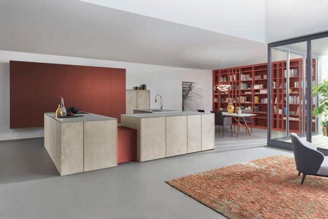 Aufmerksamkeitsstark und sehr präsent ist diese Premium-Designküche in dem erdigen, tief leuchtenden Farbton Rotocker und hellen, von Hand aufgetragenen Oberflächen, die wie echter Sandstein wirken. © AMK