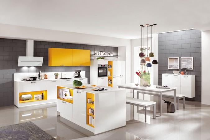 Eine Portion Sommerfeeling zaubert diese attraktive Wohnküche in Sonnengelb und Weiß in jeden Alltag. Durch die integrierte Regalbeleuchtung kommen die Farbakzente so richtig zum Strahlen. © AMK
