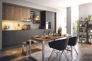 Gelungener Materialmix: Alteiche-Nachbildung kombiniert mit metallischen Oberflächen lassen diese Küche zeitlos-elegant wirken. © AMK
